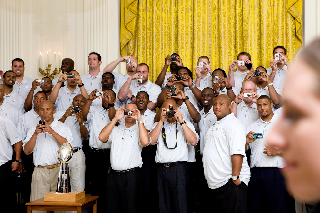 Members of the Pittsburgh Steelers take photos as President Barack Obama walks into the room